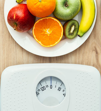 Plate of Fruit in Front of a Scale